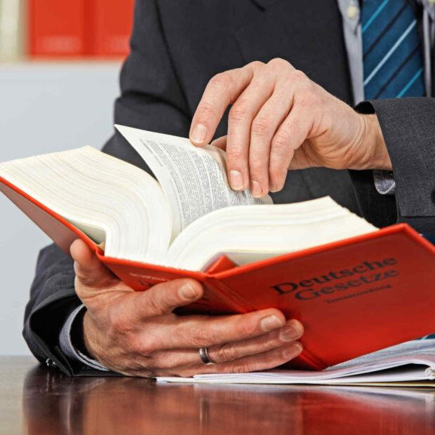 Rechtsanwalt blättert in Gesetzen - bildich für Strafrecht